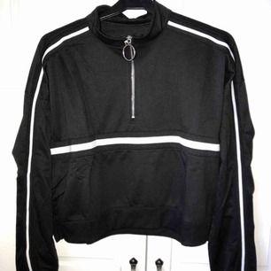 """svart långärmad """"sweatshirt"""" typ med vita ränder och liten dragkedja.  Aldrig använd pga att den inte passade. Är egentligen i en större storlek men passar Xs/s/m. Lite kroppad. Köparen betalar för frakten :)"""