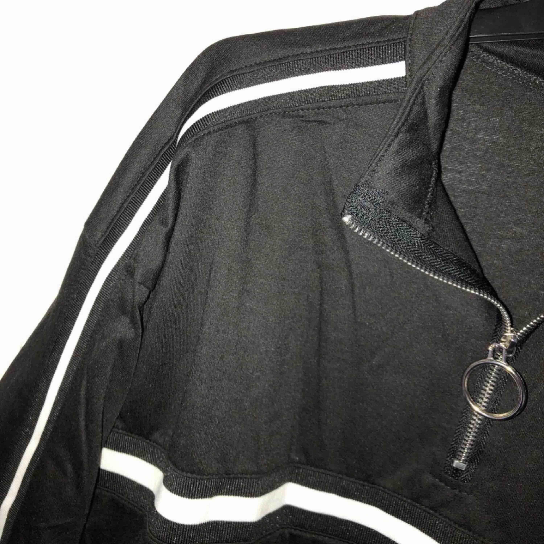 """svart långärmad """"sweatshirt"""" typ med vita ränder och liten dragkedja.  Aldrig använd pga att den inte passade. Är egentligen i en större storlek men passar Xs/s/m. Lite kroppad. Köparen betalar för frakten :). Huvtröjor & Träningströjor."""