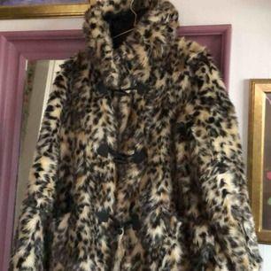 Fuskpäls i leopard mönster med luva och mellanlång modell. Stängs med knappar. Sparsamt använd.  Stl 40 men skulle säga att den är mer en 36 - 38. Postas ej, möts enbart i Stockholm.
