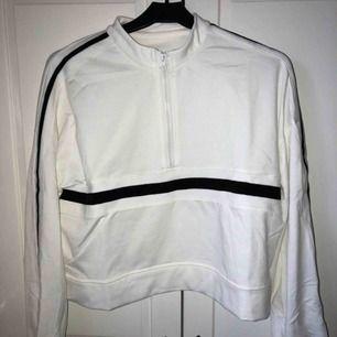 """Långärmad vit """"sweatshirt"""" typ med svarta ränder och en liten dragkedja. Aldrig använd pga att den inte passade. Är egentligen en större storlek men passar bäst till Xs/s/m. Lite kroppad. Köparen betalar för frakten :)"""