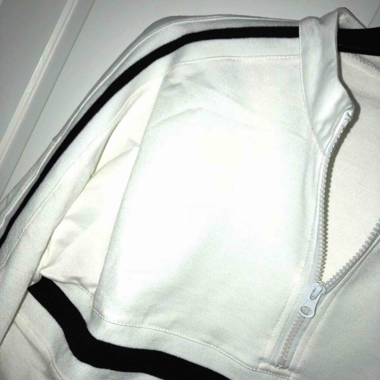 """Långärmad vit """"sweatshirt"""" typ med svarta ränder och en liten dragkedja. Aldrig använd pga att den inte passade. Är egentligen en större storlek men passar bäst till Xs/s/m. Lite kroppad. Köparen betalar för frakten :). Huvtröjor & Träningströjor."""