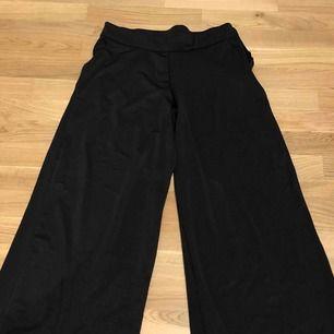 Saint Tropez byxor i fladdrigt material, glansiga med utvidga ben. Storlek XS men är stora i storleken.