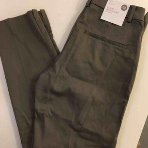 Stretchiga kostymbyxor i ankellängd. Helt oanvända. Fin slits i bensluten. Från hm. Gröna. Skickas mot fraktavgift.