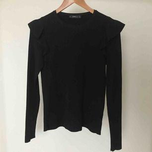 Zara ribbstickad svart tröja med volanger. Märkt med storlek L men passar en M eller mindre. 100% polyamid. Köparen står för frakt.