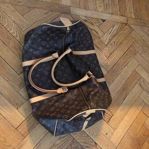 """Louis Vuitton keepall """"liknande"""" weekndbag. Har en fläck inuti, se bild, samt är skavd i hörn på undersidan och saknar en """"tass"""". Axelrem finns ej kvar"""