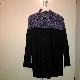 Tvådelad lång vintageskjorta. Svart nertill, blommönstrad upptill. Fin instoppad alternativt som kort klänning/blus.