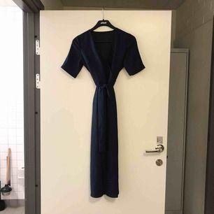 Marinfärgad klänning ifrån River Island i strl 34. Använd en gång. Knytning i midja och är lite längre än nedanför knäna.