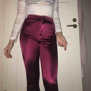 Ett par skimrande röda byxor från hm, med väldig hög midja och i stretchigt material. Pga av ljuset i bilden ser färgen mycket mörkare ut än i verkligheten.  (Tröjan till salu på min profil)