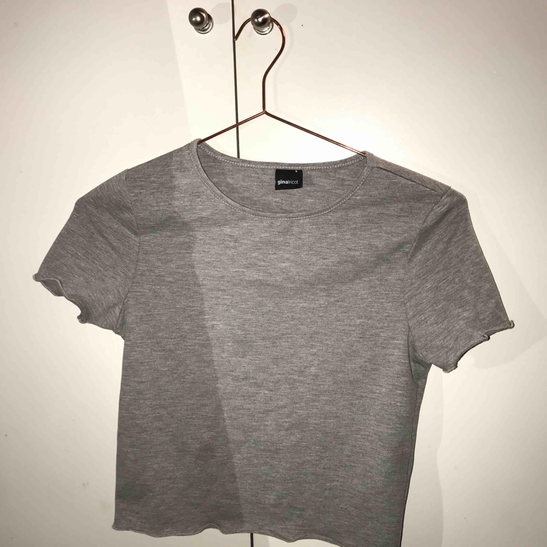 Fin grå croppad t-shirt från Gina Tricot ✨ S men ganska liten i storlek. Köparen står för frakt!. T-shirts.