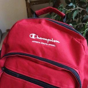 En knallröd ryggsäck från champion. Riktigt snygg, med cool färg. Den är mindre än en vanlig ryggsäck och perfekt till när man inte behöver en fullt så stor väska till ex, stan, utflykt etc. ca 30x25 cm köpt 2hand