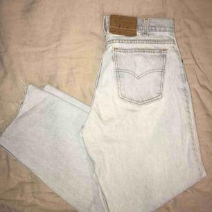 """Levi's vintage jeans i modellen """"550"""". Ljusblå/blekta i färgen och avklippta vid anklarna. Strl. 32 men kan bäras som oversized modell! Ett mindre, ihopsytt hål på knät samt en liten fläck under.  Upphämtas i Göteborg/köparen för frakten!"""