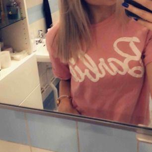 Rosa t-shirt från Berska med Barbie tryckt på bröstet.