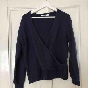 """Stickad """"cross-over"""" tröja från NA-KD. Knappast använd. Ska vara marinblå, men är enligt mig lila/marinblå. Jättemysig! Stor i storlek. Köparen står för frakten."""