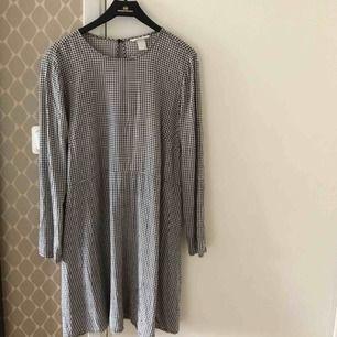Söt svart-vit-rutig klänning från hm med söm i midjan och detalj i ryggen (bild 3). Den är i vanligt begagnat skick.