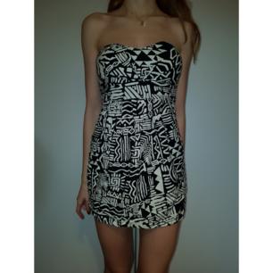 Kort klänning med svart-vitt mönster. Dragkedja på baksidan och elastisk vid bröstet. Har ett skärp som man kan knyta på ryggen( bild 2).  Möts/Fraktar 💜💜  passar bättre som XS-S