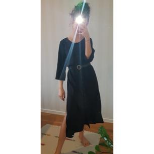 Lång, svart klänning med slits på båda sidorna och knappar på framsidan hela väggen ner (bältet ingår EJ). Materialet är väldigt bekväm och lätt.