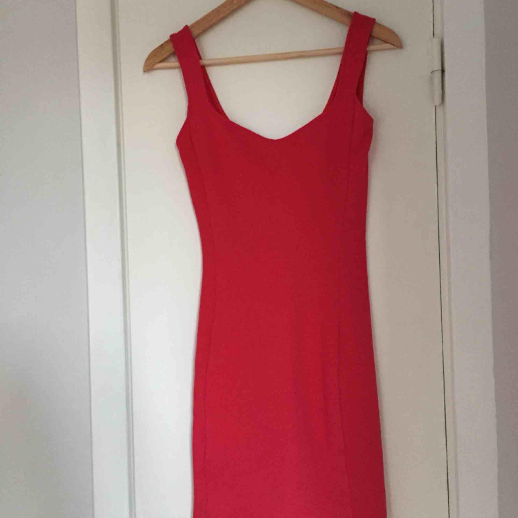 06758f6e3627 Tajt röd klänning från Bershka med fin skurning där fram. Köparen står för  frakten.