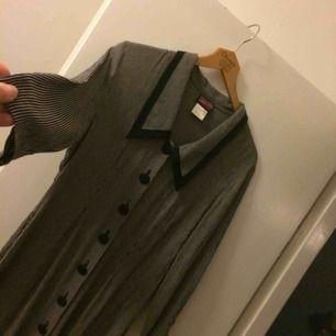 Randig figurnära vintageklänning i använt skick. Den är lagad längst ner (se bild) och knappen längst ner fattas därav det billiga priset. Varken lagningen eller avsaknad av sista knappen har stört mig vid användning!