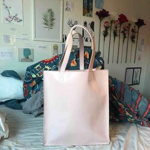 super snygg totebag ifrån monki. passar perfekt för skolan med mycket rum. den är en kräm rosa färg med långa axelremmar. har även en sidficka inuti.