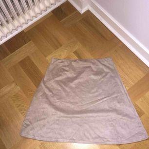 Mjuk beige kjol i sammetstyg från Nelly. Oanvänd. Köparen betalar frakten