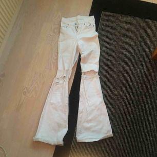 """Vita flare Dr denim jeans, modellen """"Macy"""". Sitter tight och är i stretchigt material. Lite gråa på insidan längst ned, men inget som syns när man har dem på. (Se bild). Dem har hål på knäna som är mer upprivna än vad de var från början."""