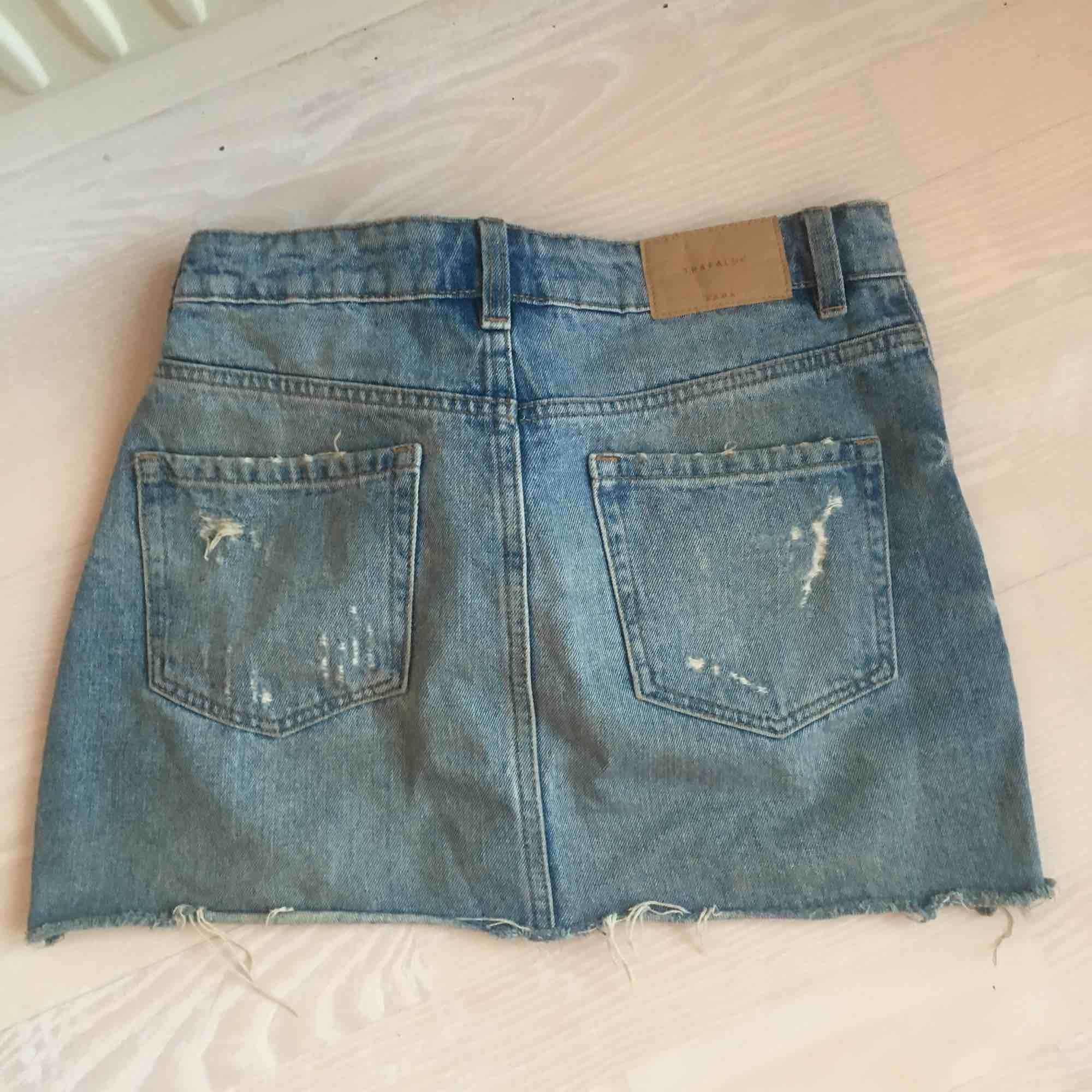Kort mellanblå jeanskjol från Zara, med slitningar. Frakt ingår inte i priset (50kr). Kjolar.