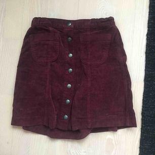 Fin kort kjol i Manchester tyg, knappar i mitten och fickor. Snygg vinröd färg! Från Brandy Melville😀 Köpare står för frakt:)