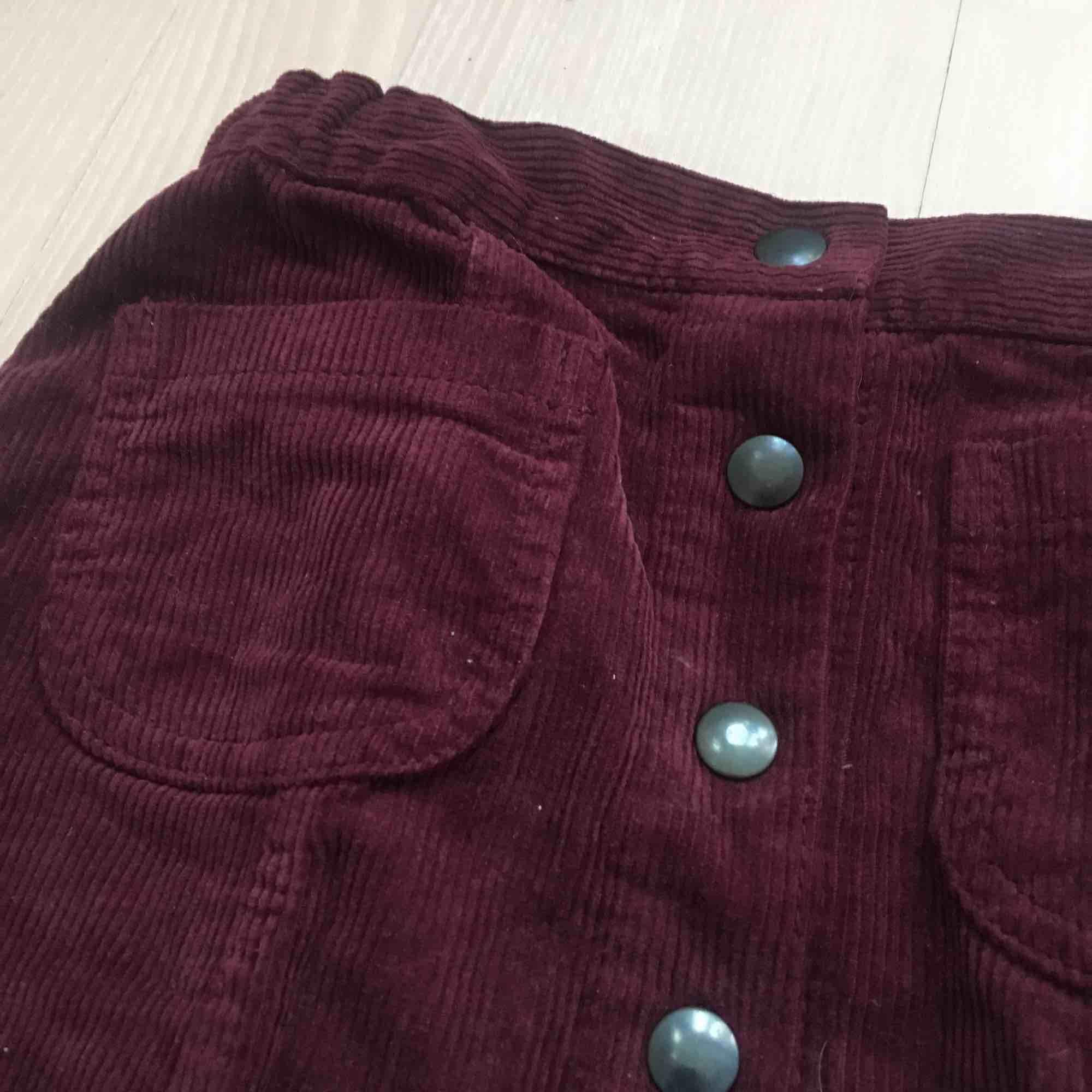 Fin kort kjol i Manchester tyg, knappar i mitten och fickor. Snygg vinröd färg! Från Brandy Melville😀 Köpare står för frakt:). Kjolar.