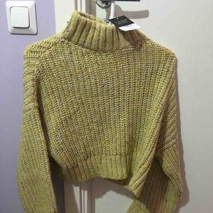 Senapsgul stickad tröja i kort modell. Nyligen inköpt men aldrig använd, prislappen sitter på. Stl 38 passar en S.