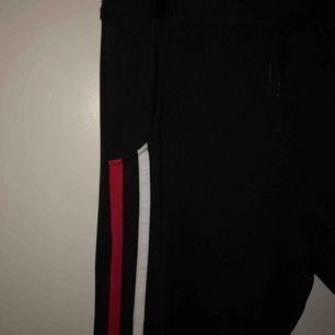 """Svarta """"mjukisbyxor"""" med en vit och en röd rand på. Ser kanske inte så fina ut på bilden men de var svåra att fota.  Är aldrig använda och är helt nya. Köparen står för frakten"""