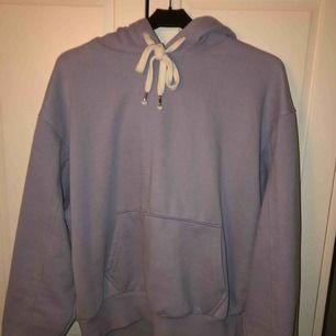 En ljusblå/lila hoodie med vita snören som jag gillar att knyta. Denna hoodien är använd väldigt få gånger.  Köparen står för frakten.
