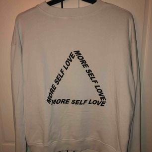 """En vit tröja eller """"sweatshirt"""" med ett tryck på ryggen.  Denna tröjan har används en gång. Köparen står för frakten."""