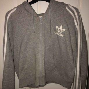 En äkta grå/vit adidas croptop hoodie.  Aldrig använd pga att den inte passade. Är egentligen större storlek men är väldigt liten i storleken. Köparen står för frakten.