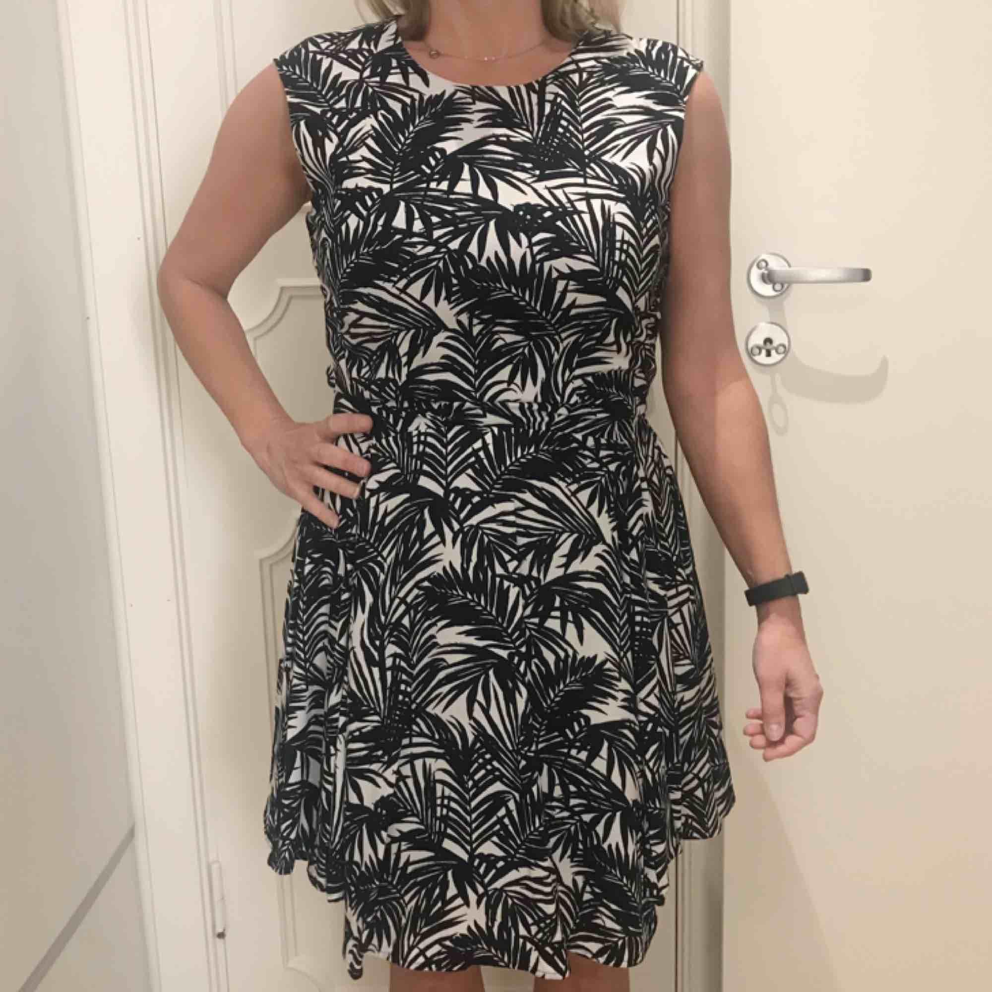 Svartvit klänning från H&M med palmblad i fint skick 🌟 frakt på 50 kr tillkommer. Klänningar.