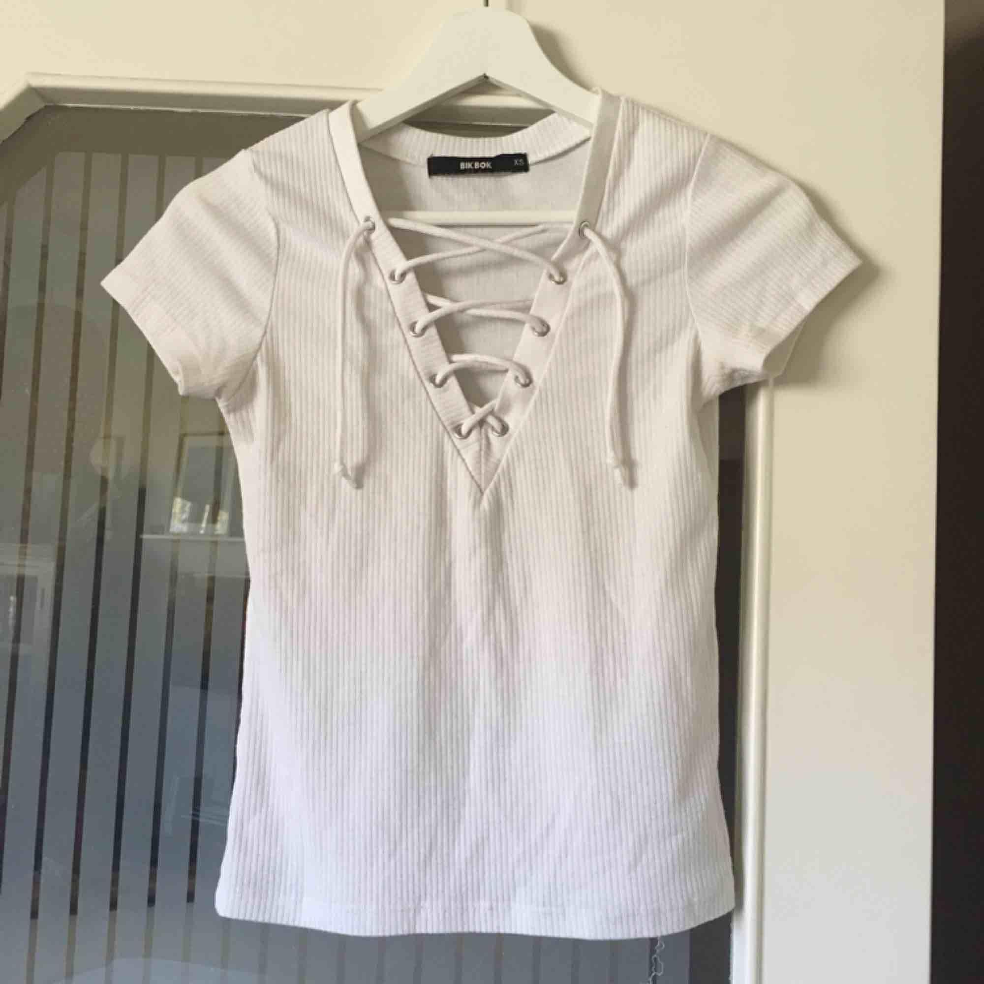Vit ribbad t-shirt med snörning, storlek XS. Knappt använd, jättefint skick! Kan mötas upp i Stockholm eller skicka mot fraktkostnad (gissar 18:- eller 39:-). T-shirts.