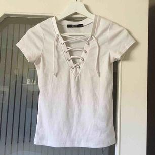 Vit ribbad t-shirt med snörning, storlek XS. Knappt använd, jättefint skick! Kan mötas upp i Stockholm eller skicka mot fraktkostnad (gissar 18:- eller 39:-)