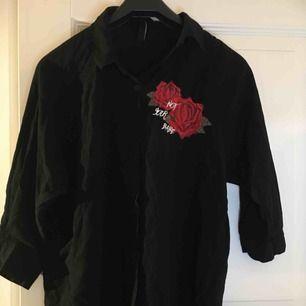 Svart skjorta med ett ros tryck som knappt är använd.  Frakt - 25kr
