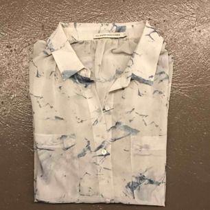 Skjorta mönstrad i vit/blå. Helt oanvänd.