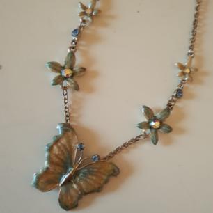 Halsband med blommor och fjäril, blåa nyanser.