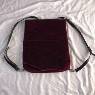 en vinröd sammetsryggsäck, använd några gånger men den har inga spår från det. banden och dragtappen är ej i riktigt läder. Formen är fyrkantig och den har ett innerfack, väldigt praktisk. säljer pga att jag ej längre använder den