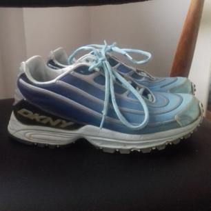Vintage coola skor från DKNY köpta på Humana i stl 38. Modellen påminner lite om Nike Air Max 97 med de lite vågiga ränderna som går runt skon. I begagnat skick, lite detaljer har börjat släppa i ränderna men tycker inte man tänker på det så mycket. Det silvriga som syns på baksidan av skon på andra bilden är reflex-material som syns bra i mörkret. Det har börjat släppa lite från DKNY-märket på insidan av skorna, inget som stör men kanske går att limma ihop. Skickar gärna bilder på det om du frågar! Frakt 63 kr.