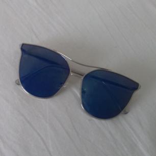 Solglasögon med silvrig båge och blått spegel-glas med lite transparens som gör att man kan ana ögonen bakom solglasögonen i vissa ljus (syns på mittenbilden). Lite skiftande färg på glaset, om det är mörkt ser dom mer blå/lila ut och när det är stark sol blir dom ljusare blå och reflekterande som en spegel. Köpta i Spanien. Frakt 39 kr.