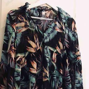 Från h&m, blå/orange/rosa blommor. Svart tröja, halvt genomskinlig med volanger och mycket detaljer. Storlek 36, passar XS och S. Superbra skick! 50kr