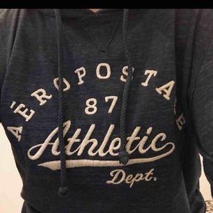 Blå hoodie som är väldigt tunn med vit text, ficka och luva. Tröjan är ifrån märket Aeropostale. Bra skick! Passar XS och S.