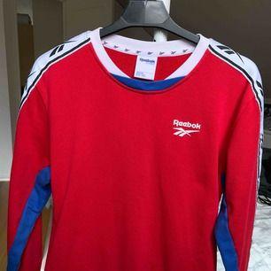 Reebok tröja i röd med vita och blåa detaljer. använd en gång och sitter väldigt bra. den har även fickor på magen