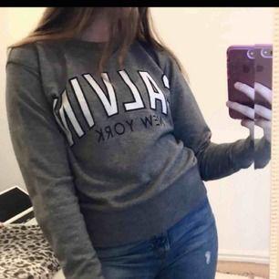 En grå crewneck / sweatshirt från Calvin Klein jeans med svart vit text. Jättebra skick - ANVÄND CIRKA 3 GÅNGER. Storlek XS. Nypris cirka 700kr tror jag, Mitt pris 250kr