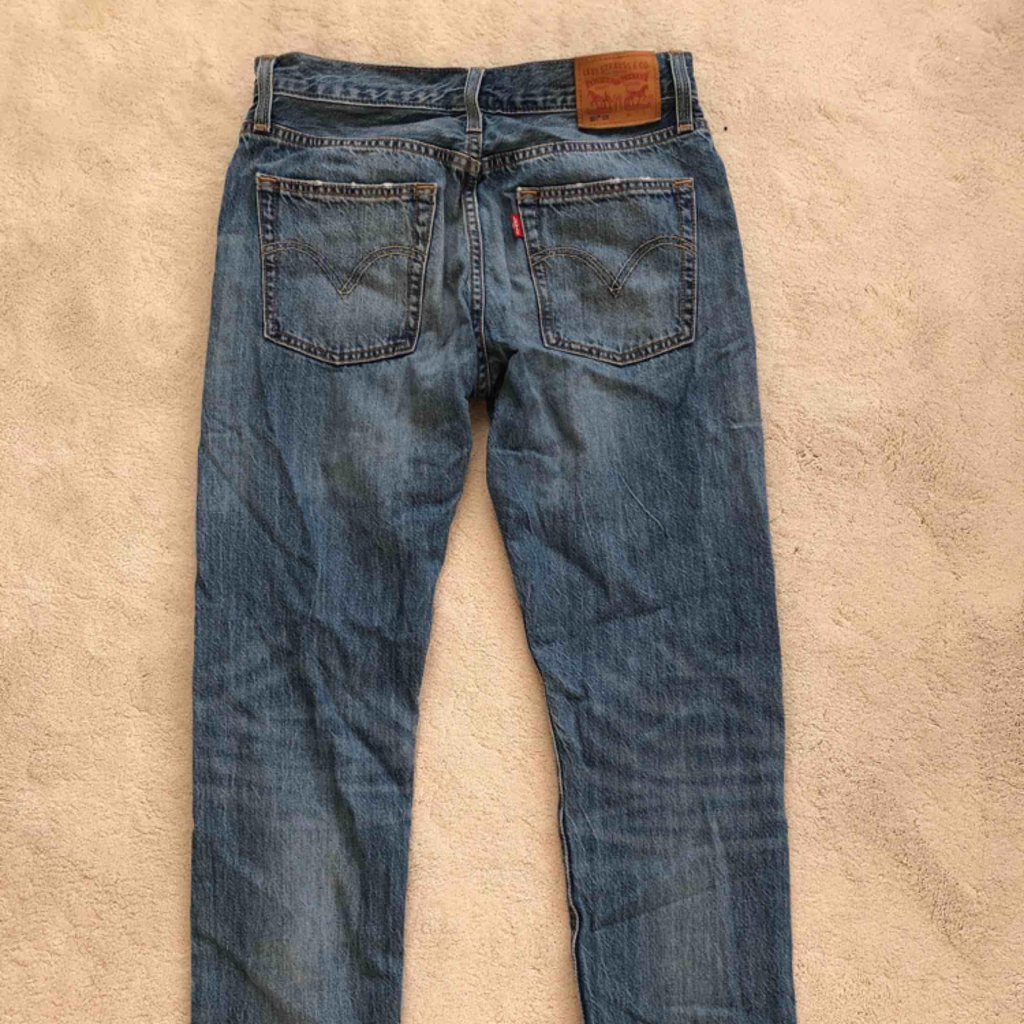 Ett par ljusblåa Levisjeans med slitningar. Modellen 501.. Jeans & Byxor.