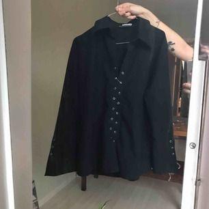 Svart skjorta, perfekt lätt oversize-modell på en storlek XS/S.  Har använt med säkerhetsnålar istället för snörning. Mkt bra skick!