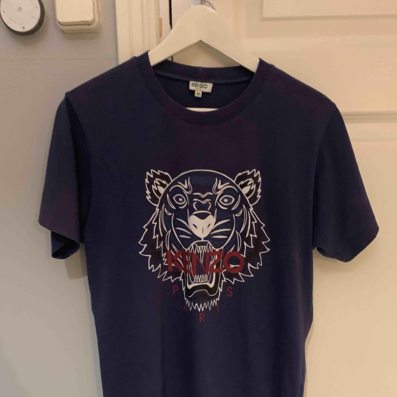 T-shirt från Kenzo i storlek M (herrmodell) med det klassiska tigertrycket. T-shirten är endast använd 1 gång så den är i mycket fint skick. Kvitto och prislappar finns kvar. Nypris hos Kenzo cirka 1000kr OBS! Köpare betalar eventuell frakt. T-shirts.