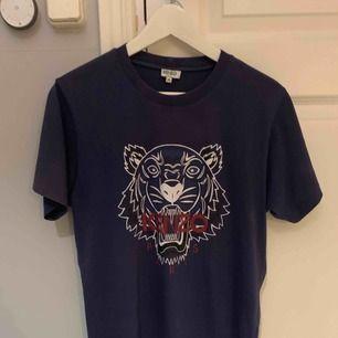T-shirt från Kenzo i storlek M (herrmodell) med det klassiska tigertrycket. T-shirten är endast använd 1 gång så den är i mycket fint skick. Kvitto och prislappar finns kvar. Nypris hos Kenzo cirka 1000kr OBS! Köpare betalar eventuell frakt